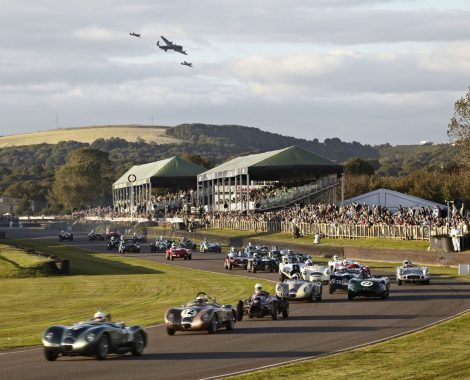 Goodwood Revival with cars and airplanes in background